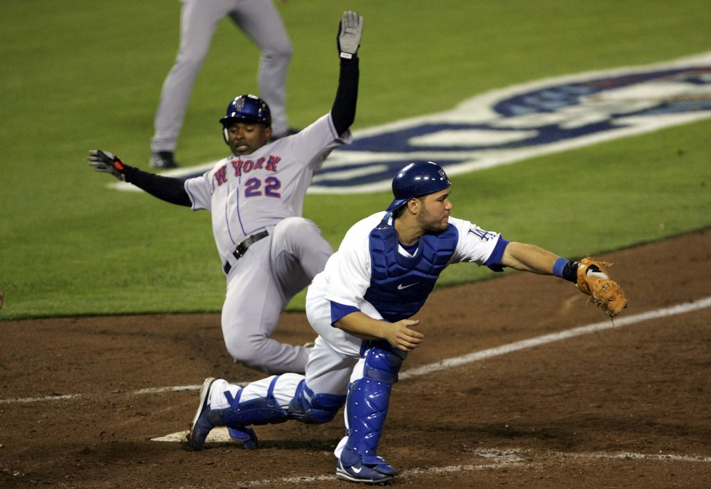 Michael Tucker slides past Russell Martin for the go-ahead run in the sixth inning of Game 3. (Stephen Dunn/Getty Images)