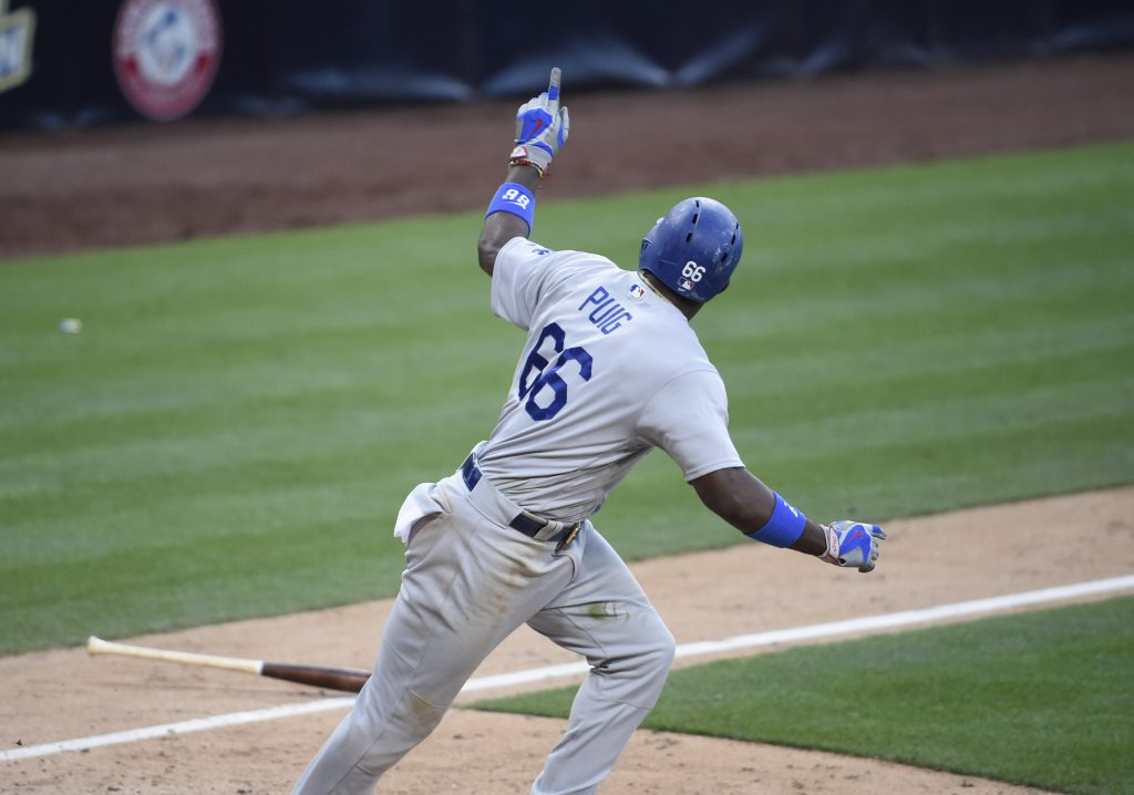 Yasiel Puig points back to the dugout after hitting a tiebreaking two-run single in the 17th inning. (Denis Poroy/Getty Images)